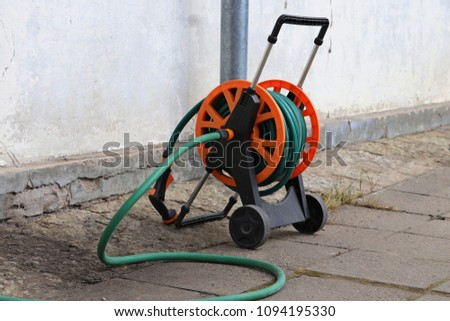 Garden hose on wheels isolated on white Images and Stock