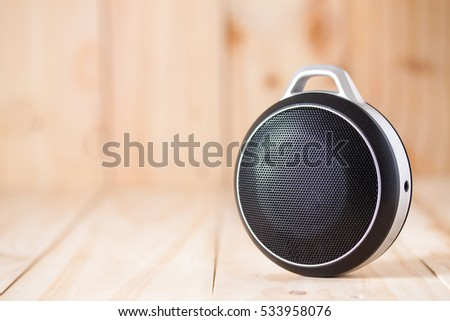 Portable or wireless speaker on wooden background #533958076