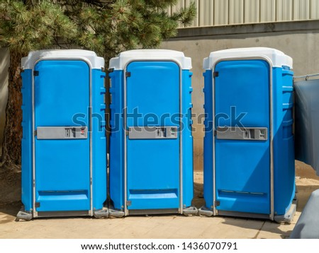Portable Public restrooms in a row against a building. #1436070791