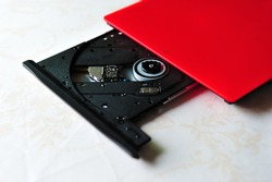 Portable slim external CD DVD burner writer isolated on white background, selective focus.