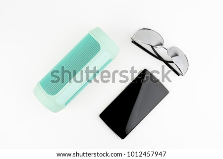 Portable Speaker With Sun Glasses And Black Smartphone On White Background #1012457947