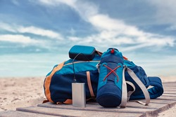 Portable travel charger. Power Bank charges a musical speaker against a backdrop of journey bags, a beach and sky with cloud. Concept on the theme of tourism