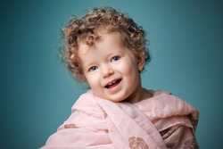 Portait of a cute, little girl looking interested wearing pink scarf in front of blue background. Color photo.