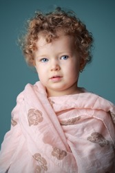 Portait of a cute, little girl with a serious look and curly hair wearing pink scarf in front of blue background. Color photo.