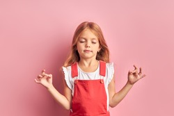 Portait of adorable little girl wearing red overalls meditating isolated over pink background