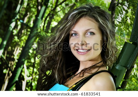 Portait of attractive young woman near green hedge