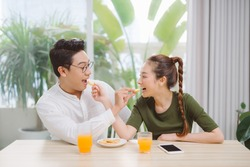 Portait of beautiful family happy man and woman having breakfast in house while sitting at table