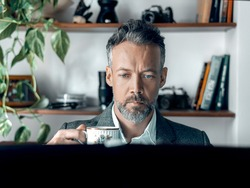 Portait of businessman drinking coffee during break and working on his computer in the home office.