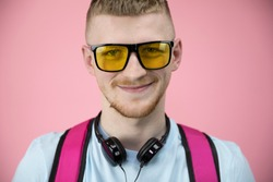 Portait of cute american boy in yellow glasses and headphones over neck broadly smiles. Close-up portrait of trendy young bearded man in t-shirt over isolated pink background