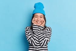 Portait of pleasant looking cheerful Asian woman keeps hands on cheeks smiles gently wears striped jumper stylish hat expresses sincere emotions isolated on blue background. Positive face expressions