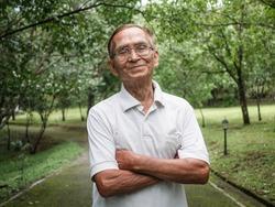 Portait of senior man enjoying nature in the park. Senior retired man enjoying the freedom of retirement.