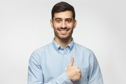 Portait of smiling businessman with thumbs up gesture, isolated on gray background