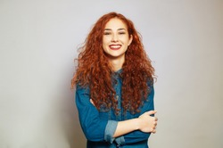 Portait of smiling redhair young woman posing with crossed arms