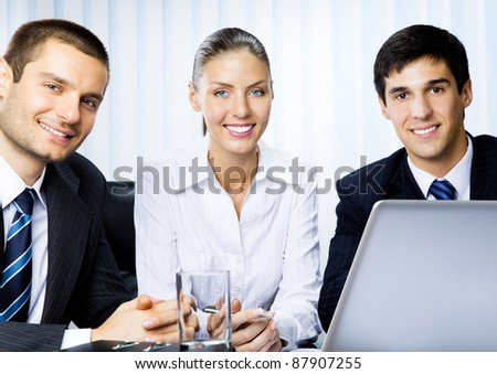 Portait of three happy smiling successful business people at office - stock photo