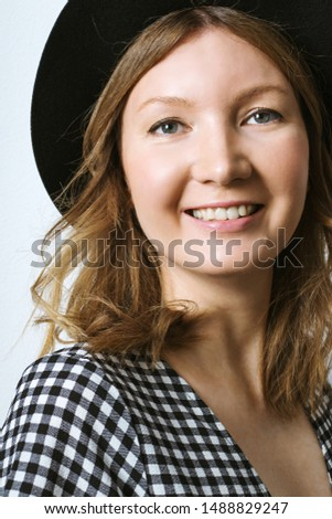 Portait of young adult toothy smiling woman dressed black hat and black and white check dress.