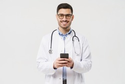 Portait of young male doctor in white coat smiling, holding his smartphone with both hands, using medical app, standing isolated on gray background