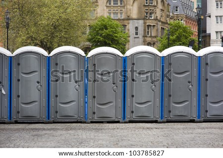 portaloos outdoors at an outdoor event in a line or row