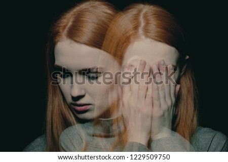 Porter of beautiful redhead girl with psychotic disorders covering her face, hiding from her hallucinations Stockfoto ©