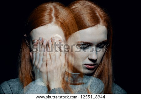 Porter of beautiful redhead girl with psychotic disorders covering her face, hiding from her hallucinations, black background behind her Stockfoto ©