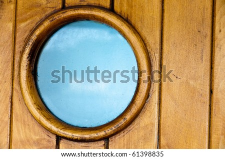 Porthole in old wooden ship's door with great blue sky visible through the glass