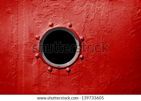 Porthole on the red wall of the old ship