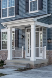Portico leading to the entrance of vinyl horizontal lap siding covered building, with a roof structure over the entryway, supported by white rectangular columns on a new single family home in Maryland