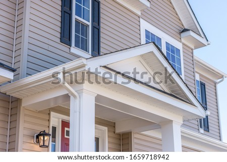 Portico leading to the entrance of vinyl horizontal lap siding covered building, with a roof structure over a walkway, supported by white rectangular columns on a new single family home in Maryland Foto stock ©