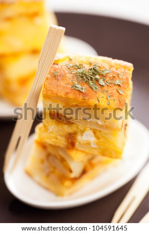 """Portion of a spanish potato omelet called """"tapa"""" or """"pincho"""",  typical spanish pub food. - stock photo"""