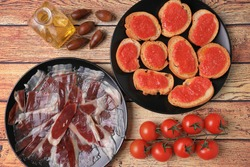 Portion of acorn-fed Iberian ham with slices of bread and tomato on black plate on wooden table decorated with olive oil, tomatoes and acorns
