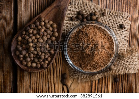 Portion of Allspice powder (detailed close-up shot) on wooden background #382891561