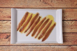 Portion of anchovies from Santoña, Cantabrian anchovies in white rectangular plate on wooden table