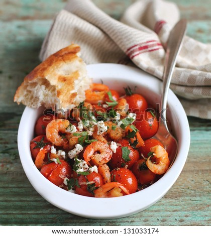 Portion of baked cherry tomatoes and roasted shrimps with greek salted ...