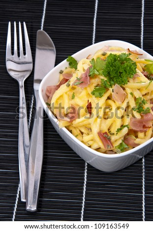 Portion of Cheese Spaetzle decorated with fresh herbs on black tablecloth
