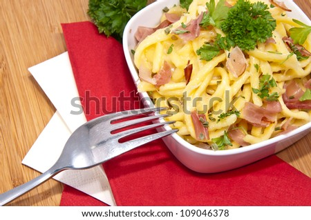 Portion of Cheese Spaetzle with cutlery (macro view)