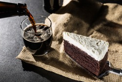Portion of chocolate cake and black beer on black background wit
