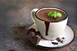Portion of homemade mint hot chocolate in a cup on a dark slate,stone or metal background.