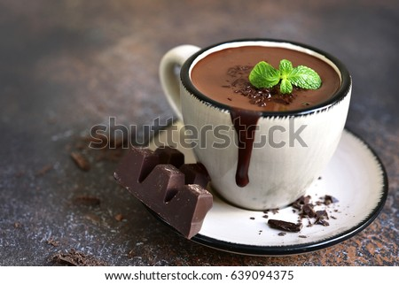 Portion of homemade mint hot chocolate in a cup on a dark slate,stone or metal background. #639094375