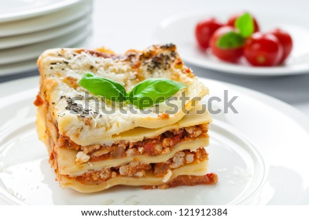 Portion of lasagna with meat topped with parmesan - stock photo
