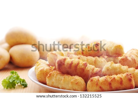 Portion of potato croquettes with raw potatoes in the background