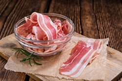 Portion of raw Bacon stripes on wooden background (selective focus)