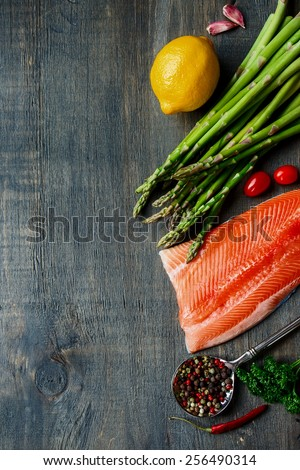 Portion of salmon fillet with asparagus and aromatic herbs, spices and vegetables over wood - healthy food, diet or cooking concept. Top view.