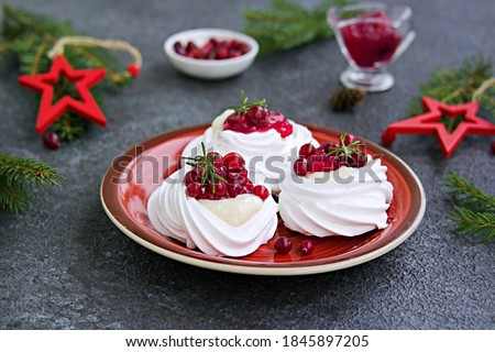 Portion Pavlova meringue pastries with cream and cranberry sauce in New Year's or Christmas decor on a red plate on a dark concrete background. New Year and Christmas desserts. Meringue recipes Foto d'archivio ©