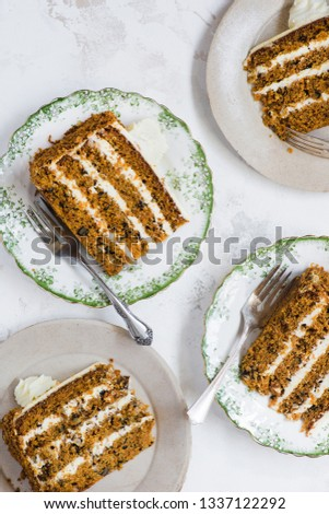 Portions of carrot cake with nuts on plates, light background, overhead, top view