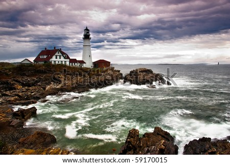 Portland Head Lighthouse sits on the edge of the Atlantic Ocean while the waves crash on the rocky coast