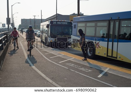 PORTLAND, OREGON August 08 2017, People biking and driving along a road before the Hawthorne bridge in the morning. a woman watches for a gap in the bike traffic after getting off the bus. #698090062