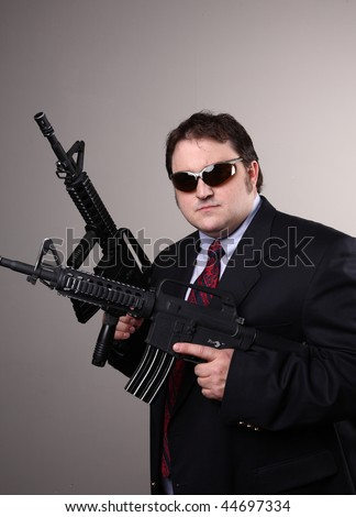 Portly mobster wearing suit and holding assault guns.