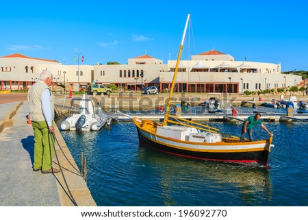 PORTO GIUNCO PORT, SARDINIA - MAY 27, 2014: fishing boat returns from open sea to Porto Giunco port. Many fishermen anchor boats here and sell fresh fish to restaurants in the harbour.