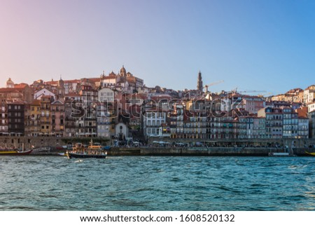 Porto, Portugal - Douro river with old boat and city skyline with colorful houses at summer sunset