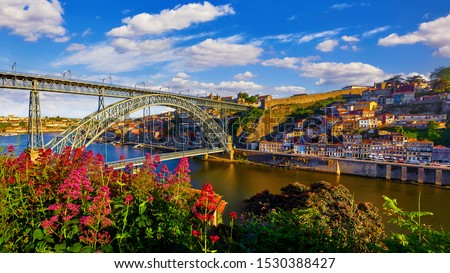 Porto, Portugal. Evening sunset picturesque view at old town with antique houses and red roofs near bridge Ponte de Dom Luis on river Douro. Stockfoto ©