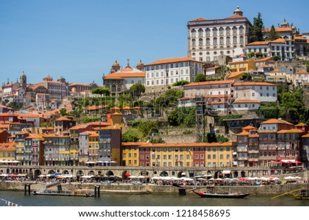 Porto, Portugal - June 14 2018 : View of the beautiful colourful houses on the waterfront by the river Douro in the old  district of Ribeira on a cloudless summer day  #1218458695
